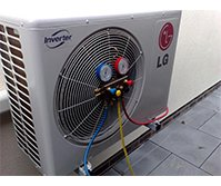 grey LG inverter with a large circlular fan shape on the left of the rectangular shaped inverter with the LG logo top left